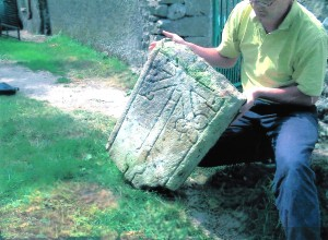 Archaeologist examining medieval graveslab found at Cloneen